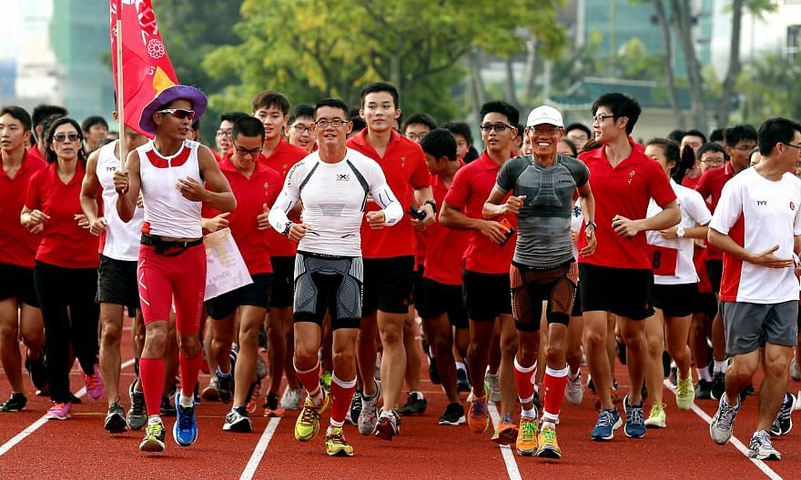 Pacer Gerrard Lin bearing the SEA Games flag as Mr Yong Yuen Cheng (centre, in white) and Mr Lim Nghee Huat (in grey) ran with students in Hwa Chong Institution yesterday.