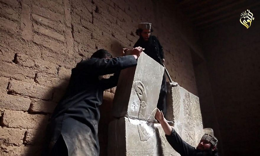 An image grab taken from a video made available by Jihadist media outlet Welayat Nineveh on April 11, 2015, allegedly shows members of the Islamic State (IS) militant group destroying a stoneslab with a sledgehammer at what they said was the ancient