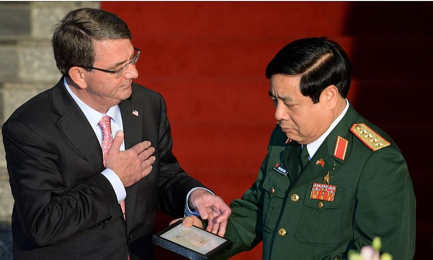 US Defense Secretary Ashton Carter (left) hands over to Vietnamese Defense Minister General Phung Quang Thanh a diary and a belt belonging to Vietnamese communist soldiers combating in the Vietnam War during a joint press conference at the Ministry o