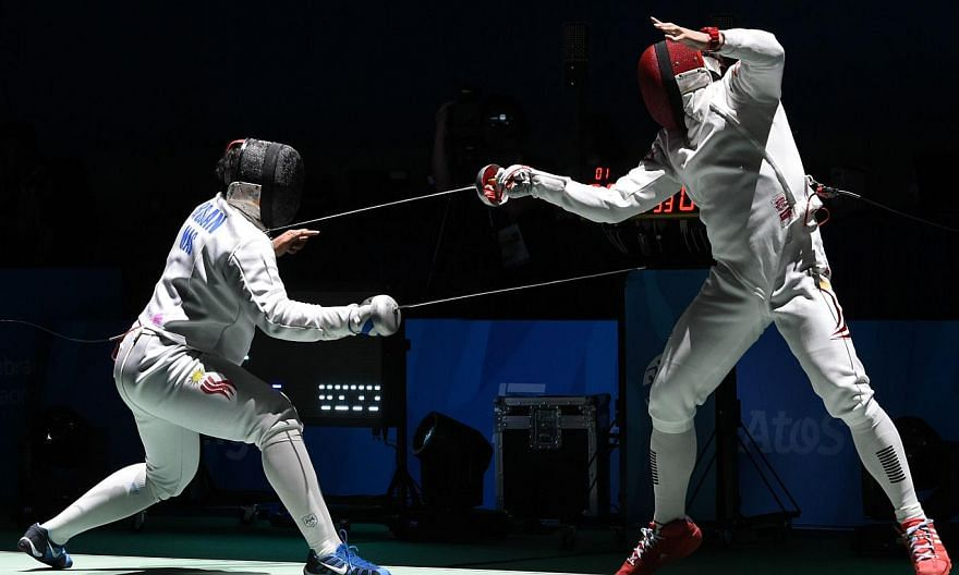Malaysia's Mohamad Roslan Mohamed (left) competes with Singapore's Lim Wei Wen (right) in their men's individual epee round of 16 fencing match during the 28th Southeast Asian Games (SEA Games) in Singapore on June 3, 2015. -- PHOTO: AFP
