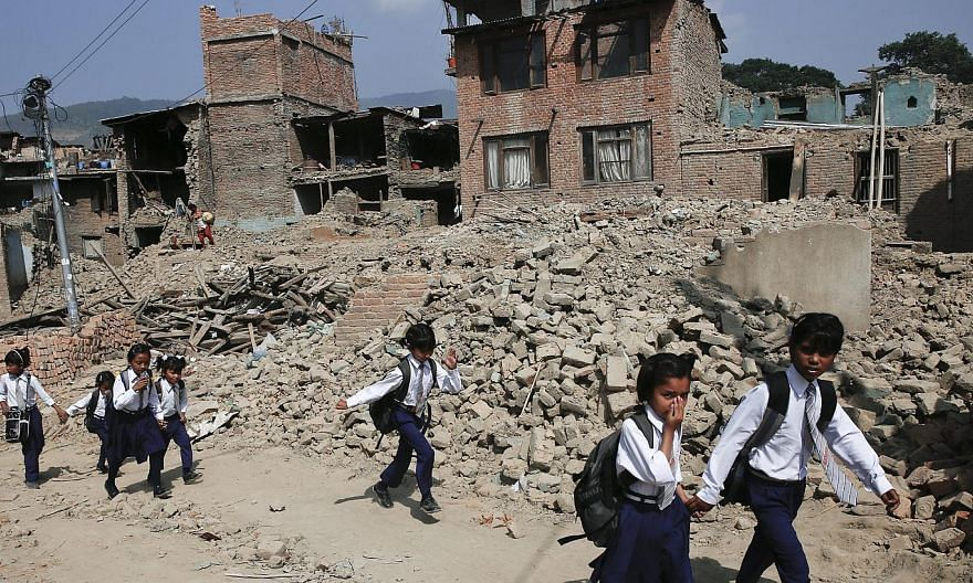 Nepalese children pass damaged houses in Bungmati, Kathmandu, Nepal on May 31,2015, which were damaged by the earthquake on April 25,2015. -- PHOTO: EPA