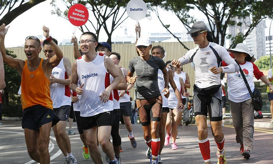 Ultramarathoners Lim Nghee Huat (in grey) and Yong Yuen Cheng (in white long-sleeved shirt), with representatives from Deloitte, finishing their 49th leg at Fort Canning Park yesterday. The pair's support crew follow behind them, stopping every kilom