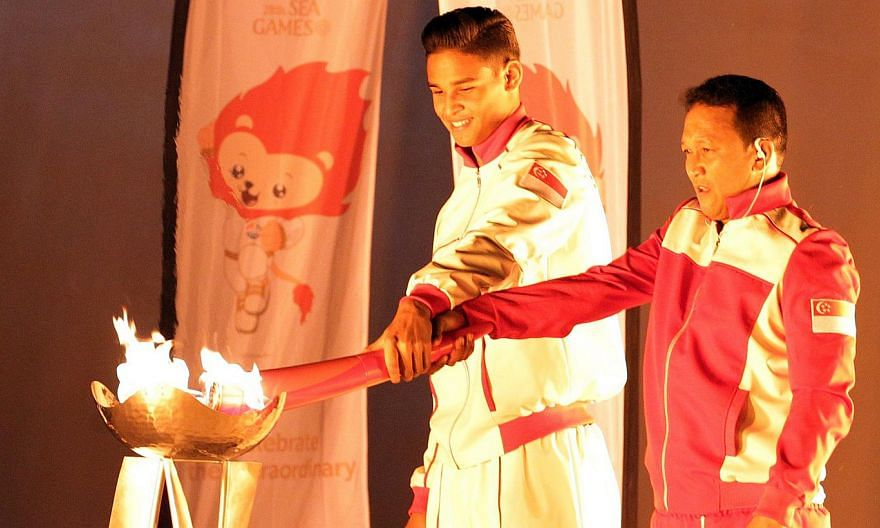 Former national footballer Fandi Ahmad (right) lighting the SEA Games cauldron with his eldest son Irfan Fandi. -- ST PHOTO: SEAH KWANG PENG
