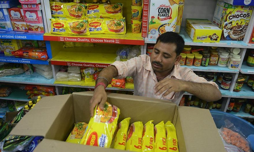 An Indian shopkeeper removes packets of Nestle Maggi instant noodles from the shelves in his shop in Siliguri on June 5, 2015. India's food safety regulator on June 5 banned the sale and production of Nestle's Maggi instant noodles over a health scar