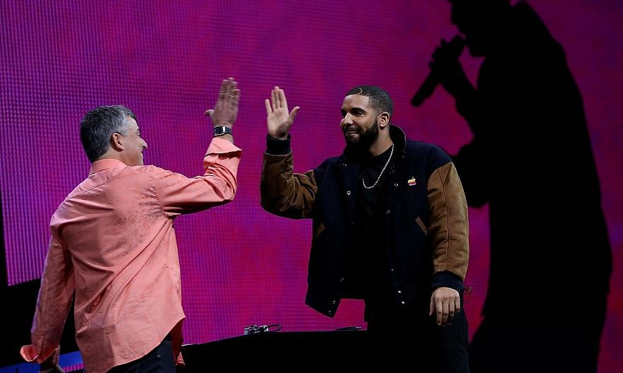 Apple's senior vice president of Internet Software and Services Eddy Cue (left) high-fives Drake during the Apple Music introduction at the Apple WWDC on June 8, 2015, in San Francisco, California. -- PHOTO: AFP