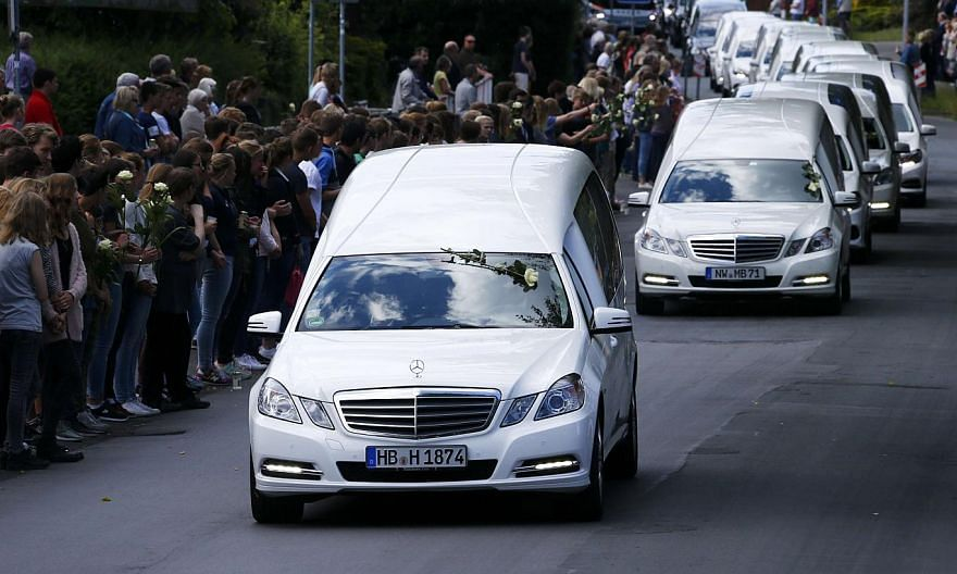 Hearses carrying the remains of victims of the Germanwings plane disaster drive past the Joseph-Koenig-Gymnasium high school, where 16 of the victims went to school, in Haltern am See, Germany, on June 10, 2015. -- PHOTO: REUTERS