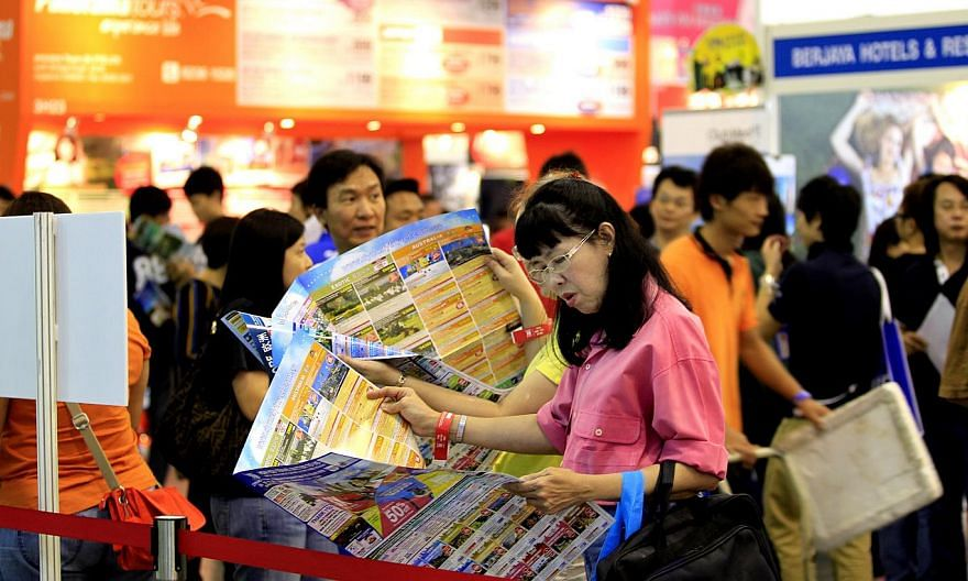 A woman looks through a tour brochure at a travel fair in Singapore. The Singapore Tourism Board announced a new licensing condition on Friday so that - from July 15 - all licensed travel agents will have to seek the decision of outbound leisure cust