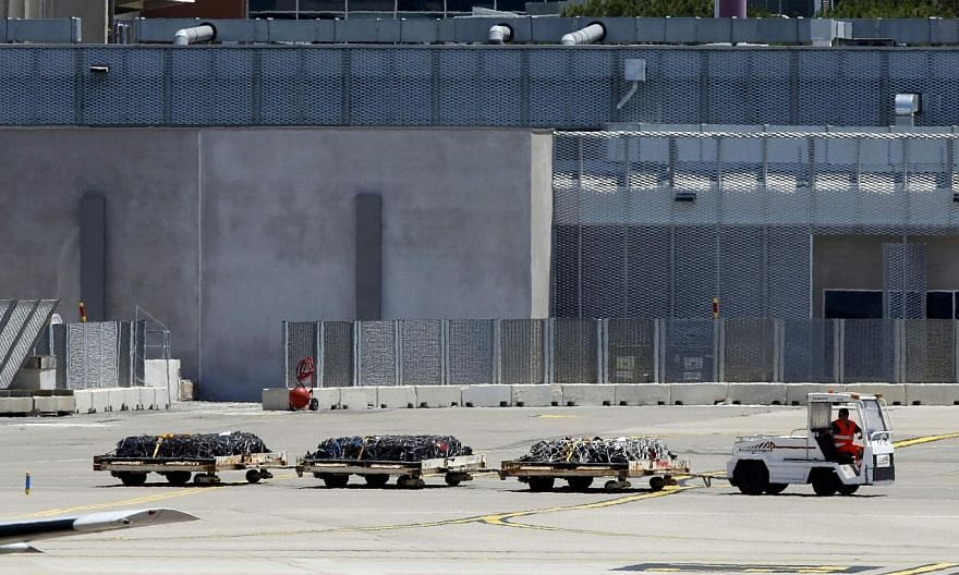 An airport vehicle pulls three cargo platforms with coffins on the tarmac at the Marseille Provence Airport in Marignane, France on Monday as Lufthansa prepares to transport coffins with the remains of 30 victims of the Germanwings Airbus A320 crash