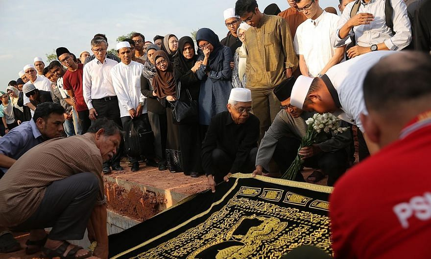 The burial (top) of Mr Mohammad Ghazi Mohamed (right) at the Pusara Aman cemetery yesterday. He leaves behind his wife Khalidal Huda Sukaimi, a teacher at East View Secondary School, and three children.