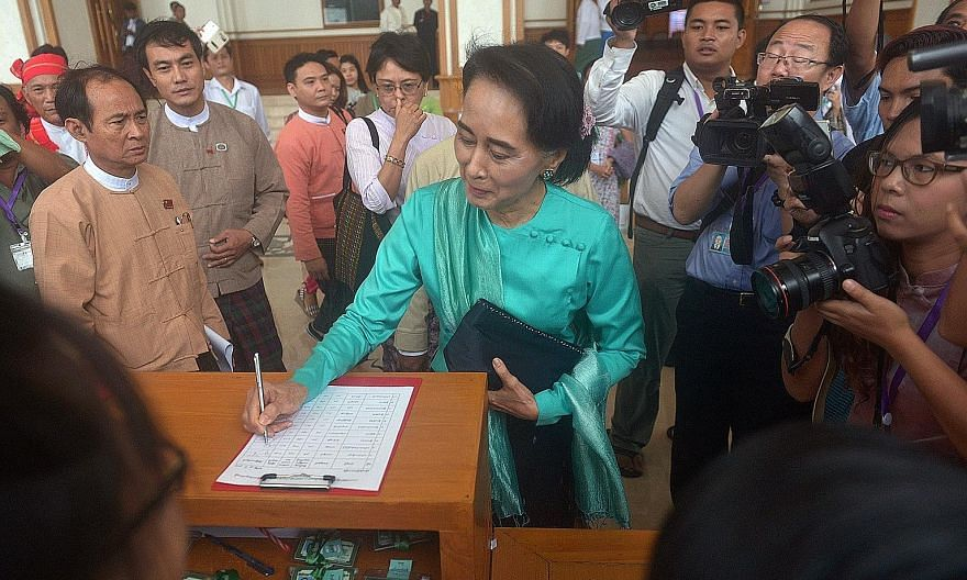 """Ms Suu Kyi registering before attending a Parliament session yesterday. She urged people not to """"lose hope"""" after the failure to amend the Constitution, saying the opposition would not """"back down"""" from elections."""
