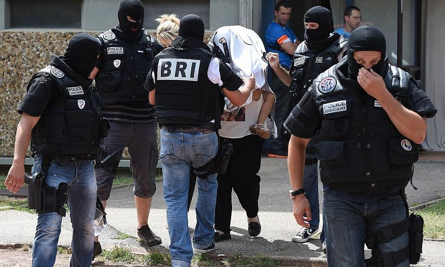Special forces of France's Research and Intervention Brigades (BRI) escorting an unidentified woman and child yesterday as they left the building where the suspect lived. France's Interior Minister said Yassin Sahli had been under surveillance on sus