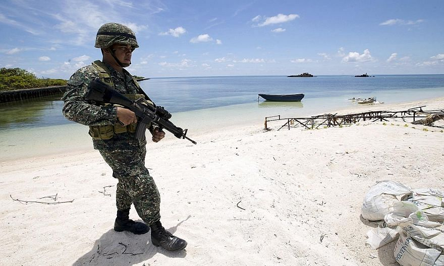 A Filipino soldier patrolling the shore of Thitu Island. The airstrip on the island has deteriorated, but the Philippine government has halted repair works on it due to its pending suit at The Hague.