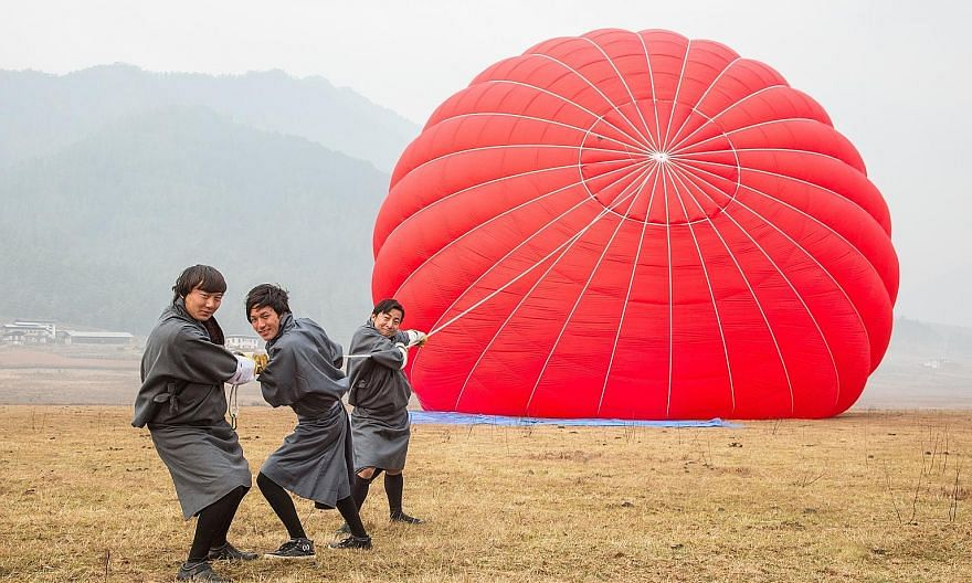 Bhutan's monasteries, such as this one on the left, have not been overrun by mass tourism. The 400-year-old multi-tiered Gangtey Goenpa monastery (above) stands on a ridge. Balloon pilot Cary Crawley (above, centre) with Mr Brett Melzer and his wife