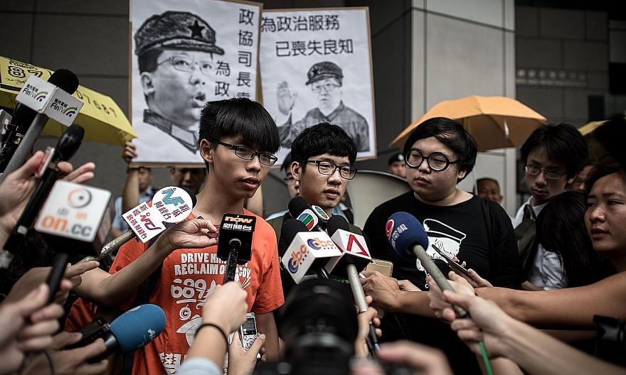"""Hong Kong student leader Joshua Wong (far left) is accusing the authorities of a witch-hunt against those at the forefront of the """"Umbrella Movement"""". He is facing several charges for his role in the protests."""
