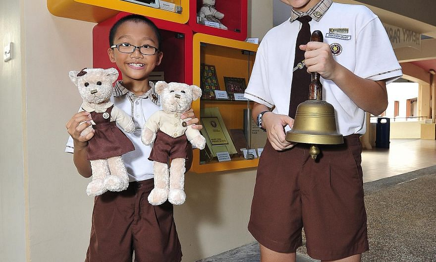 Primary 5 pupil Ryan Tan displays two plush toys dressed in uniforms worn by pupils between 1986 and 2002, while Primary 6 pupil Benjamin Lilley shows off an old school bell.