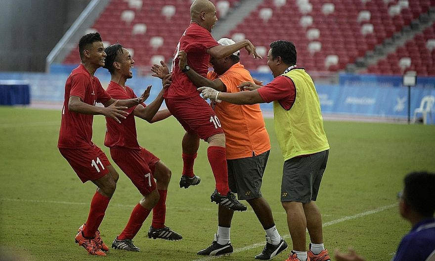 Singapore's cerebral palsy football team captain Khairul Anwar Kasmani (lifted) celebrating after scoring a last-gasp goal with just a minute left in the 1-0 win over Indonesia.