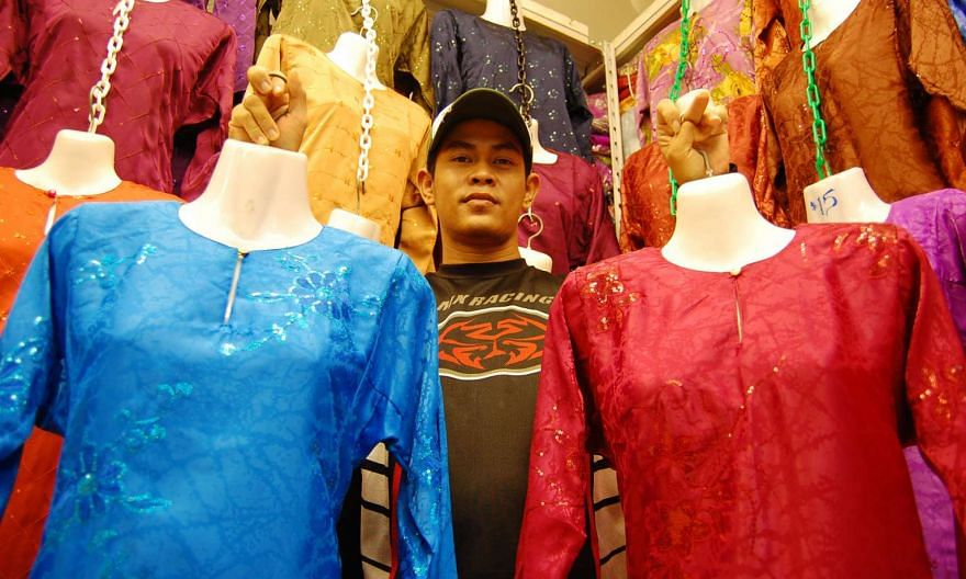 A stallholder in Geylang Serai holding up two traditional Malay costumes which were made in Vietnam.