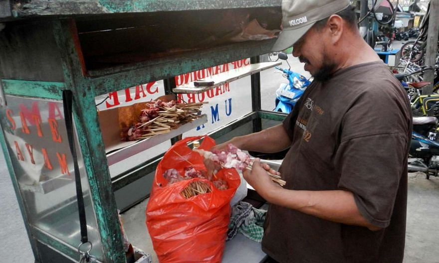 In this picture taken on Nov 4, a food stall owner prepares goat satay for his costumers in Jakarta.