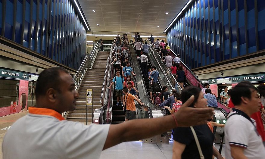 A staff member directing the crowd at Bukit Panjang station. Rides starting and ending on the Downtown Line will be free till Jan 1.