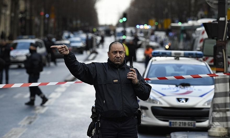 "A French policeman redirecting traffic at the Boulevard de Barbes in the north of Paris yesterday after a knife-wielding man attempted to attack a policeman at the reception of a police station in Paris ""before being hit by shots from the police""."
