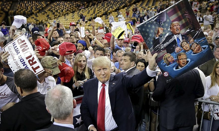 Texas Senator Ted Cruz at a rally on Saturday in Wichita, Kansas. He took the states of Kansas and Maine. Republican presidential candidate Donald Trump showing off a painting a supporter gave him at a campaign rally in Orlando, Florida, on Saturday.