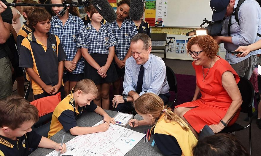 Leader of the Australian opposition Bill Shorten (centre) and Labor candidate Cathy O'Toole (right), visiting Heatley State Primary School as part of the 2016 election campaign in Queensland. Mr Shorten promised to increase scholarships to train more