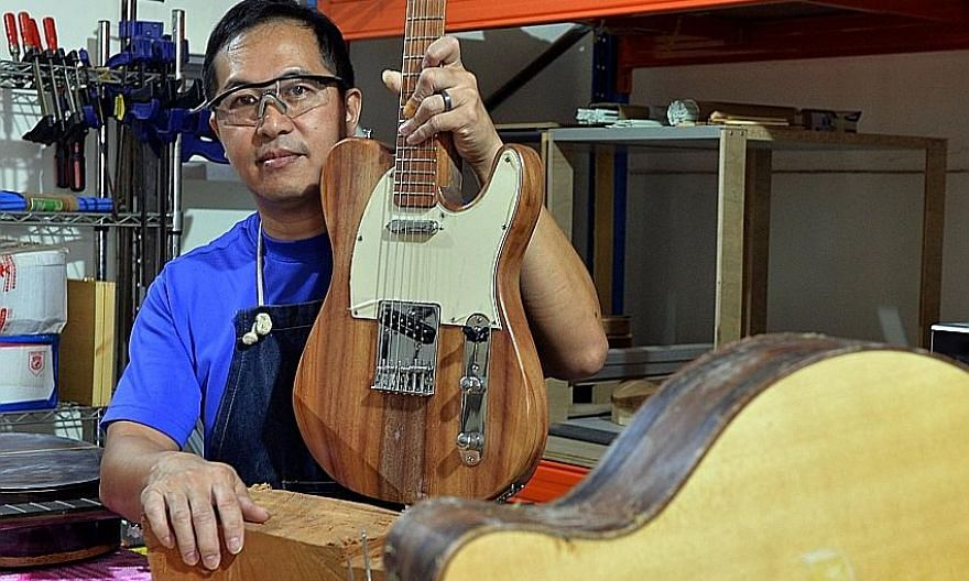 """Mr Chan with the electric guitar he made from a 25m-tall Senegal mahogany tree that once stood next to the F1 Pit Building at Marina Promenade. The tree-lover feels that having a """"tangible"""" and """"cool"""" object will help spread the conservation message"""