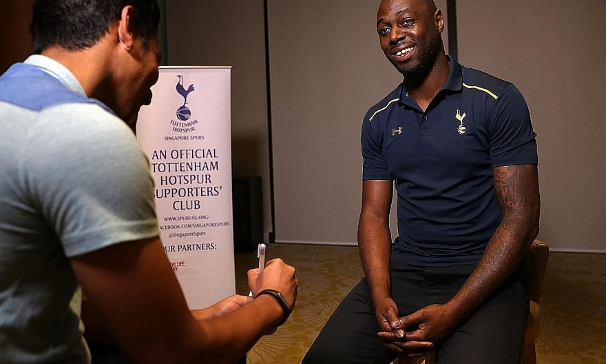 "From top: Former England and Tottenham defender Ledley King at a function at the Ramada Singapore hotel yesterday. He endorsed the Three Lions' new boss Sam Allardyce as ""a forward-thinking manager"". King autographing an old Spurs jersey for Singapor"