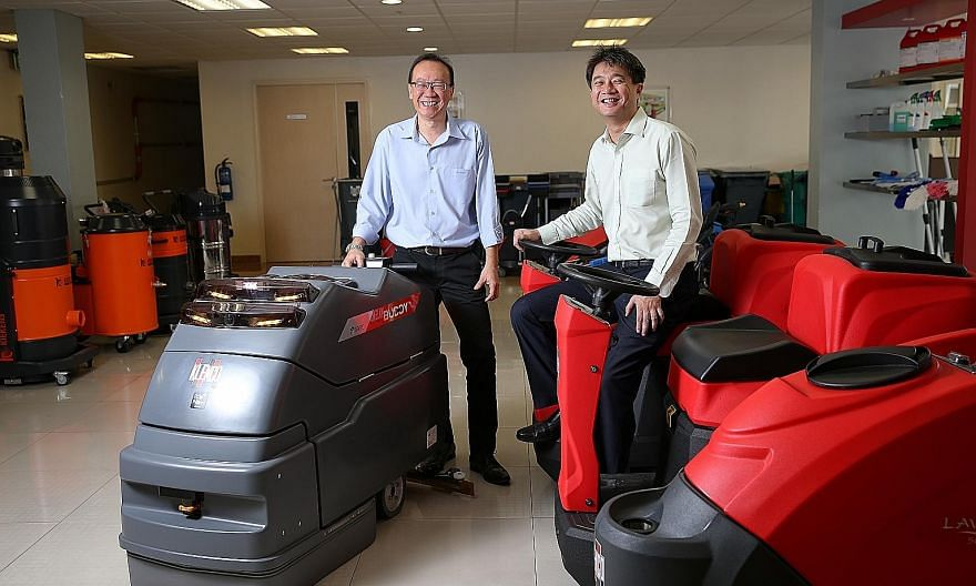 Mr Tan (far left) and Mr Beh with their robotic cleaning products. Mr Beh says the company has seen growth in demand because the use of such robots can lead to productivity gains and manpower savings.