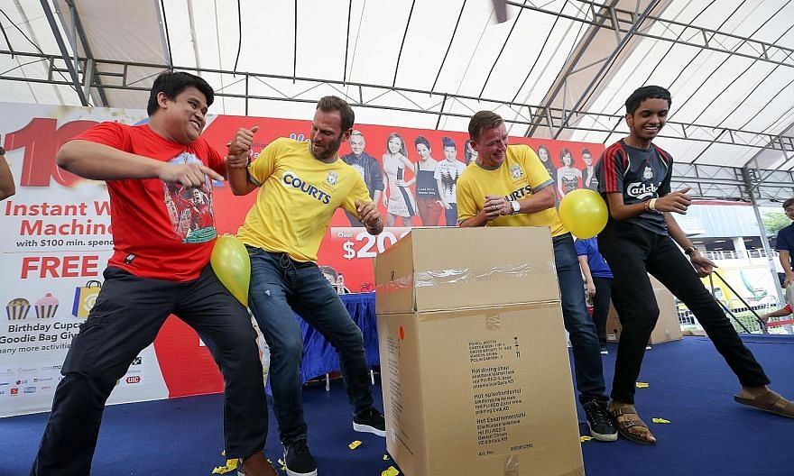 Retired Liverpool players Patrik Berger (second from left) and Vladimir Smicer showing they are good Czech-mates with fans, in a game to burst balloons at a meet-and-greet session at Courts Megastore.