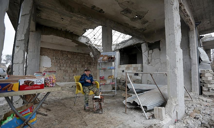 A young Syrian sweet seller warming himself by a fire in a damaged building in Aleppo on Christmas Day. Events this year have shown the new arbiters of the Middle East to be Russia, Turkey and Iran.