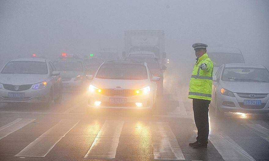 A traffic policeman working in heavy smog in Anhui province, China, on Sunday. The establishment of a national network to monitor air pollution levels coincides with government efforts to suppress reports about the country's choking pollution which a