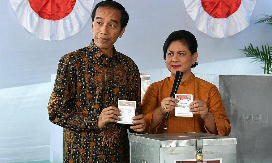 President Joko and First Lady Iriana casting their votes at a polling station in Gambir, near the presidential palace in the capital.