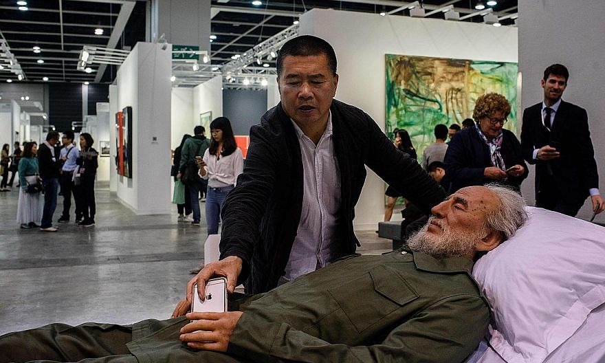 Chinese artist Shen Shaomin with a replica of former Cuban leader Fidel Castro at Art Basel in Hong Kong.