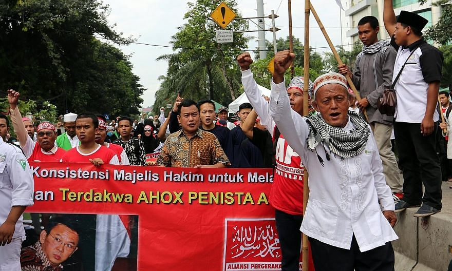 Right: Protesters marching at a rally against Jakarta Governor Basuki Tjahaja Purnama in the capital yesterday. Below: Basuki at the North Jakarta District Court yesterday. He is on trial for blasphemy and faces up to four years' jail if found guilty