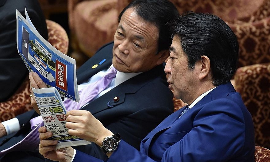Finance Minister Taro Aso (left) and Prime Minister Shinzo Abe are both special advisers to Nippon Kaigi's parliamentary league.