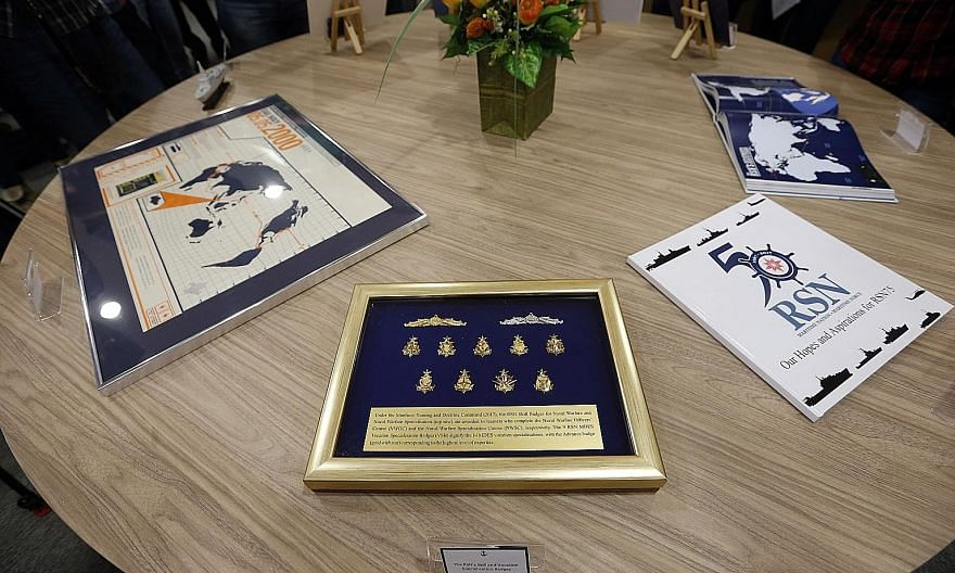 Items that will be in the time capsule include (from far left) a poster marking the ports of call during the Republic of Singapore Navy's first voyage around the world, the RSN's skill and vocation specialisation badges, a compilation of hopes and wi