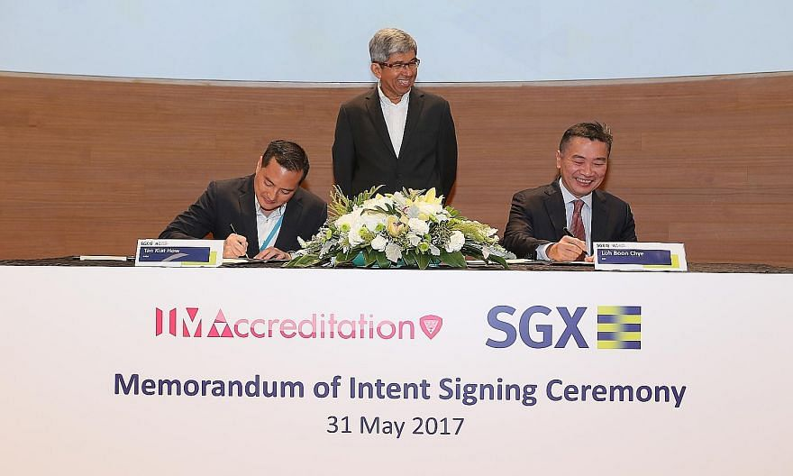 IMDA chief executive Tan Kiat How and SGX chief executive Loh Boon Chye signing a memorandum of intent to help high-tech start-ups. With them is Minister for Communications and Information Yaacob Ibrahim.