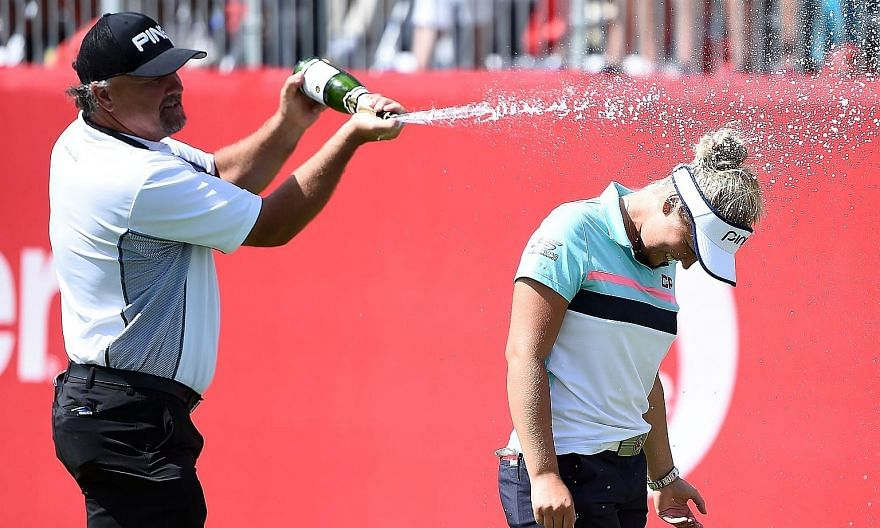 Canadian teen Brooke Henderson is sprayed with champagne by her father Dave, who is also her coach, after finishing with a 17-under 263 to win the Meijer LPGA Classic at Blythefield Country Club by two strokes from Lexi Thompson and Michelle Wie.