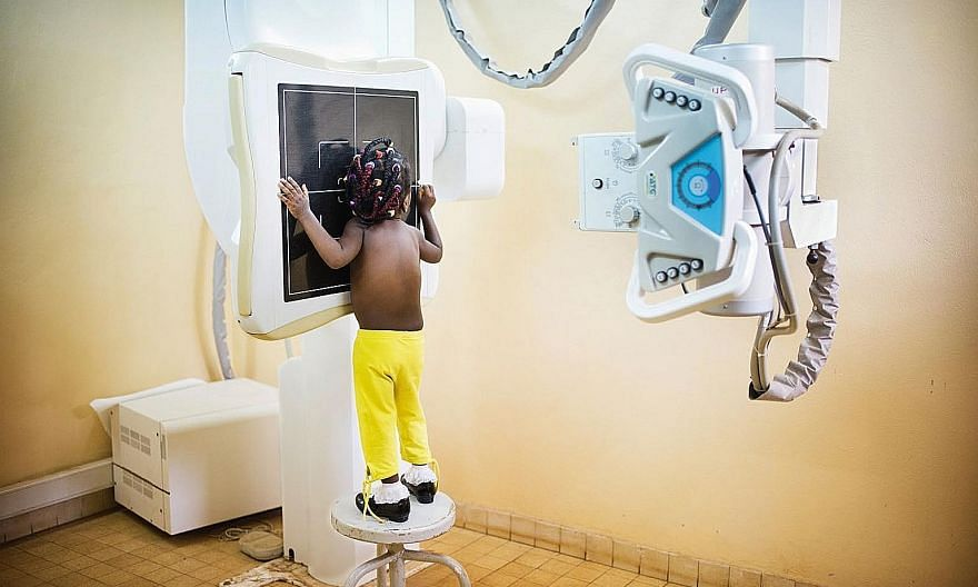 A girl needs a stool to have her X-ray taken because a power cut means the machine could not be adjusted. With Pristem's machine (below), a generator ensures it can work for a few hours in a power cut.