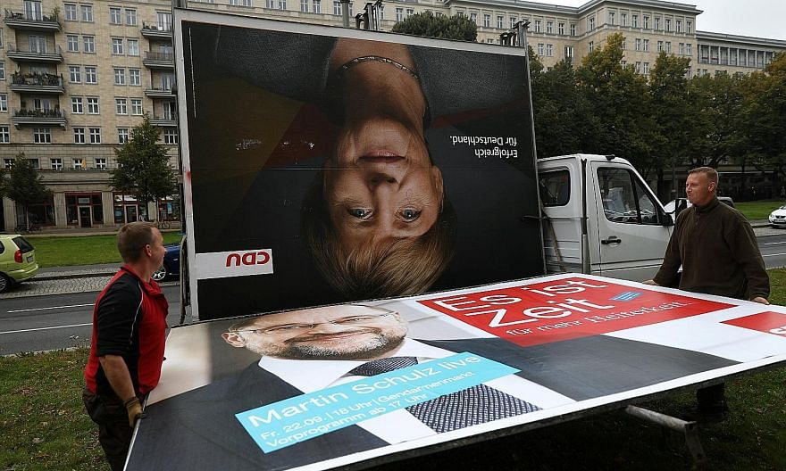 Workers removing campaign billboards for Germany's election which saw Chancellor Angela Merkel winning a fourth term but without a majority in Parliament on Sunday. The rise of the far-right Alternative for Germany party and its entry to Parliament a