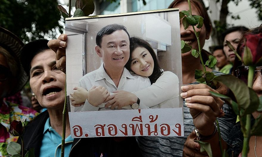 A woman holding a picture of former Thai prime ministers Thaksin and Yingluck Shinawatra. The military government has pursued supporters of the Shinawatras and has jailed several leaders of the political movement that backed them.