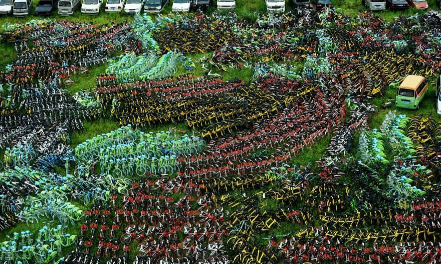 Different-coloured bicycles of various bike-sharing services parked in a village in Hangzhou, China's Zhejiang province.