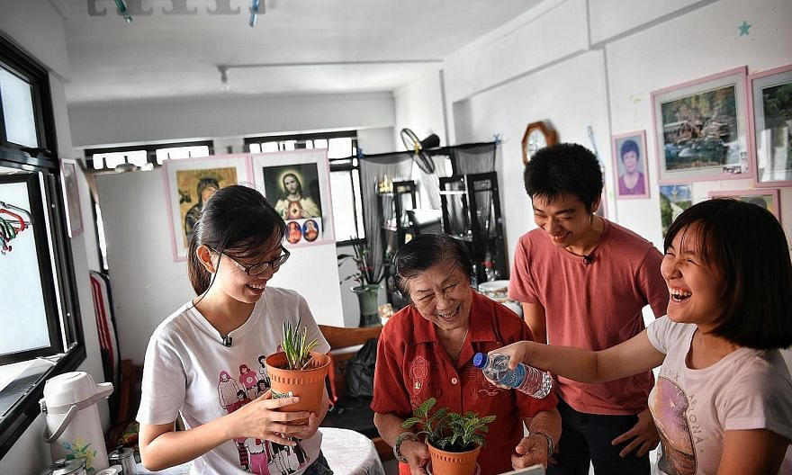 Madam Yee Dew Eng at her new Cassia Crescent home last month with Cassia Resettlement Team members (from left) Lee Wei Ting, 20, Lim Jingzhou, 20, and Ng Xiang Yun, 17. CRT volunteers visit her on Saturdays and help her pack her medication.