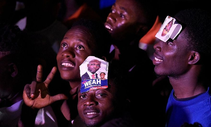 Liberians celebrating (top) as former football superstar George Weah (above) won the presidential run-off election on Thursday.