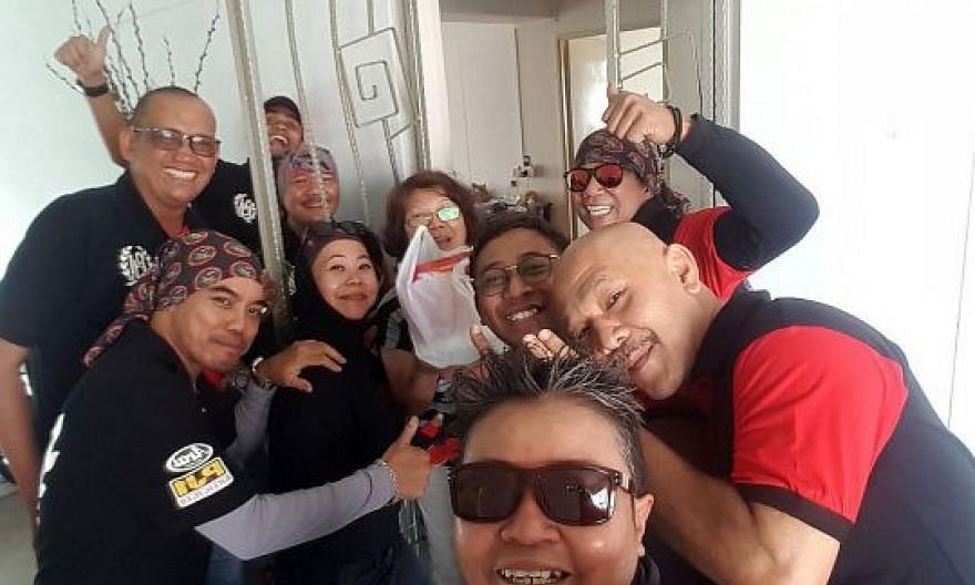 Volunteers, including biker group members, with a resident in Woodlands on the first day of Chinese New Year last Friday. They distributed packs of food mainly to elderly Chinese living alone, as well as those who are less mobile, but there were also