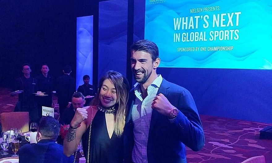 Mixed martial arts fighter Angela Lee with retired American swimming legend Michael Phelps at the Marina Bay Sands Expo and Convention Centre last night. Phelps, 32, the most decorated Olympian in history with 28 medals, was a special guest at the in