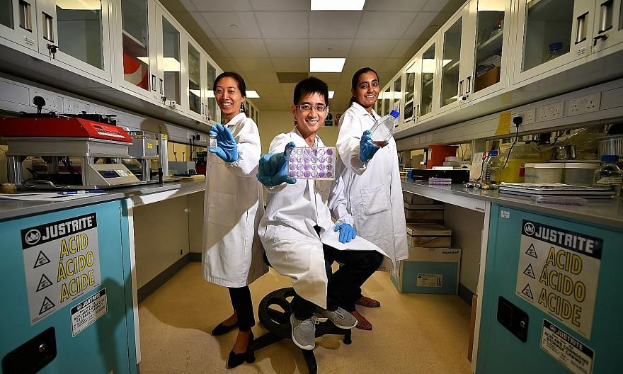 (From left) Principal scientist Debbie Lee with a vial of Tyzivumab, assistant director Chionh Yok Hian with a multi-well plate demonstrating the effectiveness of Tyzivumab against the Zika virus, and laboratory manager Rasvinder Kaur with a flask of