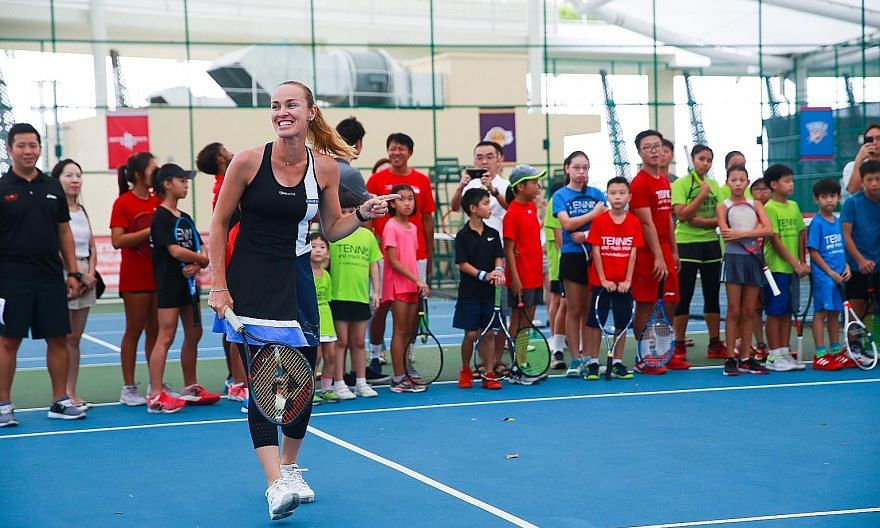Former world No. 1 Martina Hingis enjoying herself during a coaching session for 40 young tennis players from ActiveSG at Heartbeat@ Bedok yesterday.