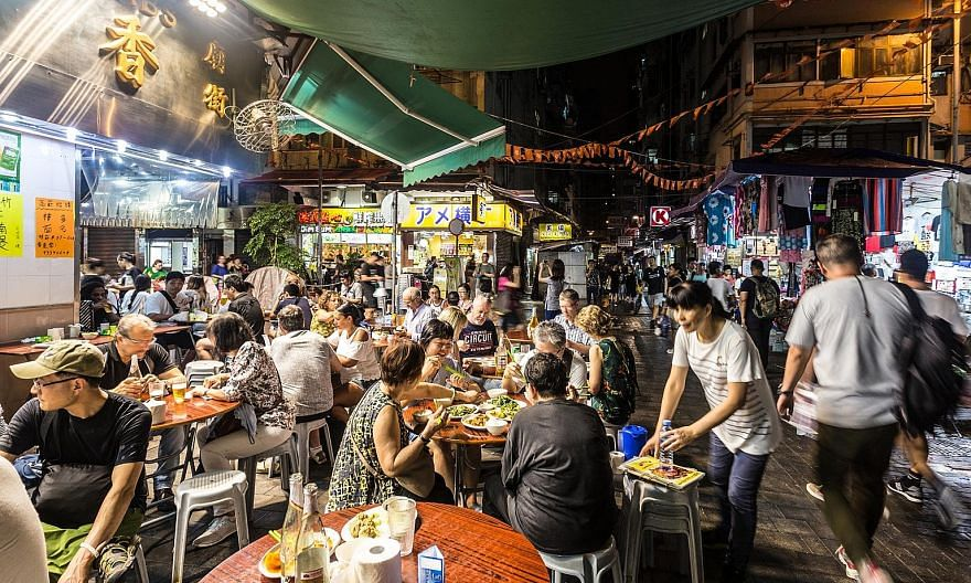 Tourists and locals dining at a street near the famous Temple Street Night Market in Hong Kong.